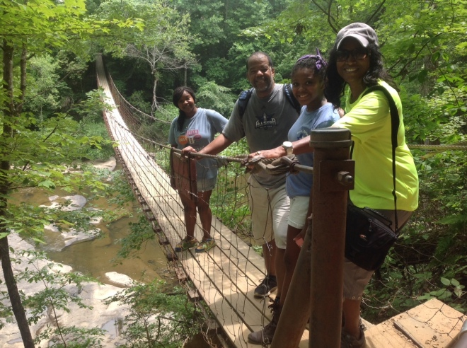 "Hiking ""Indiana Jones"" style crossing the suspension bridge in the forest."