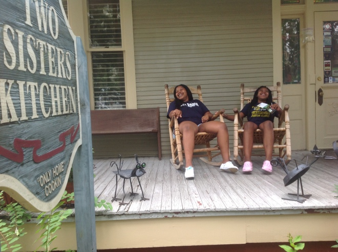 """Two sisters"" enjoying a laugh on the front porch in rockers at ""Two Sisters Kitchen"" restaurant in Jackson, MS."